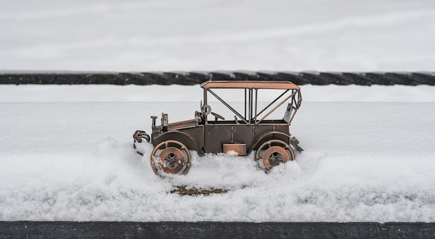 Modelo de juguete de un coche retro atascado en la nieve en una calle del parque