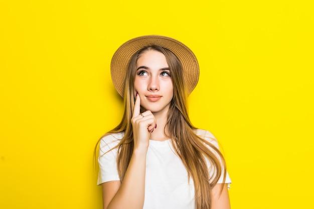 Modelo lindo en camiseta blanca y sombrero entre fondo naranja con cara divertida