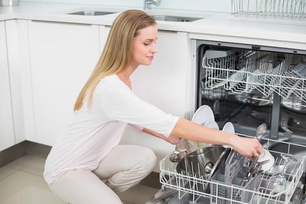 Modelo magnífico tranquilo arrodillado junto a lavavajillas