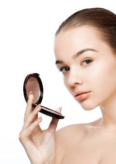 Modelo de maquillaje de belleza con contenedor de base de polvo con reflexión sobre fondo blanco.