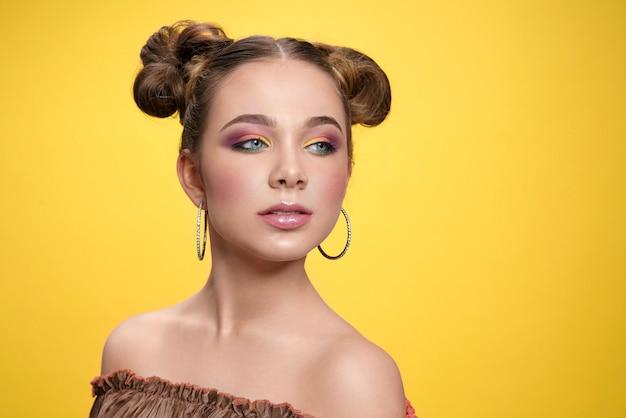 Modelo con maquillaje de colores brillantes y elegante peluquería.