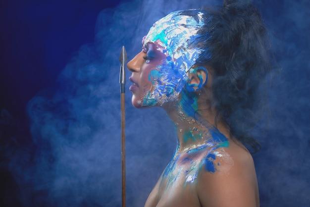 Una modelo con maquillaje fantástico y brillante, que mantiene una flecha cerca de su cara. se para en una nube de humo en la pared azul oscura y parece un personaje de fantasía.