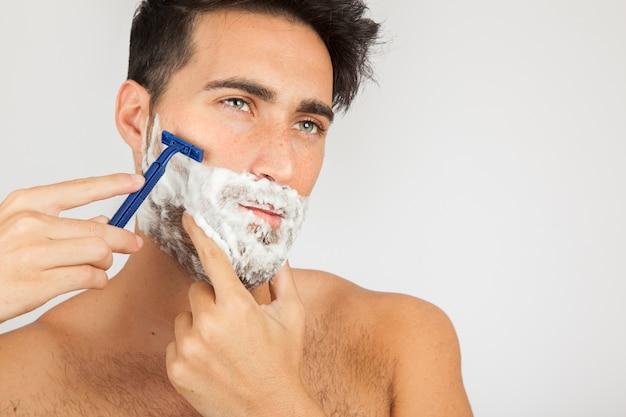 Modelo masculino afeitándose la barba