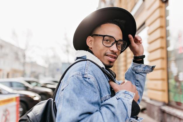 Modelo masculino africano alegre tocando su sombrero negro y mirando a otro lado en la ciudad. hombre mulato alegre con mochila caminando por la ciudad en la mañana.