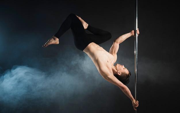 Modelo masculino atractivo realizando un pole dance