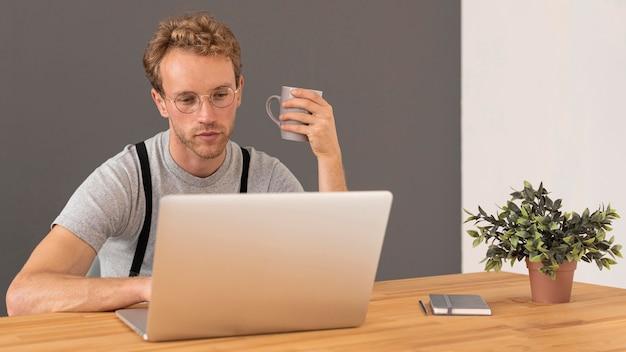 Modelo masculino con cabello rizado trabajando en su computadora portátil