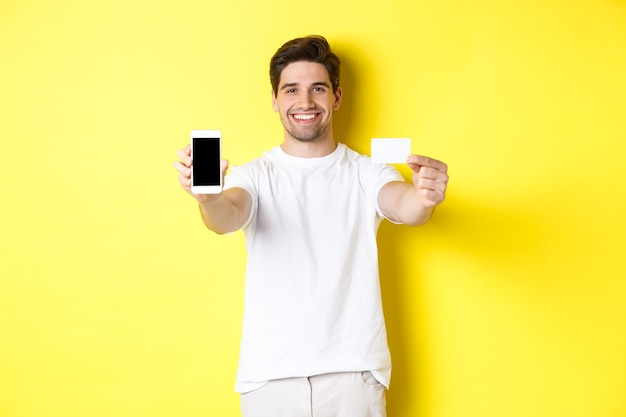 Modelo masculino caucásico hermoso que muestra la pantalla del teléfono inteligente y la tarjeta de crédito, el concepto de banca móvil y compras en línea, fondo amarillo.