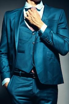 Modelo masculino elegante joven elegante del hombre de negocios en un traje que ata la corbata