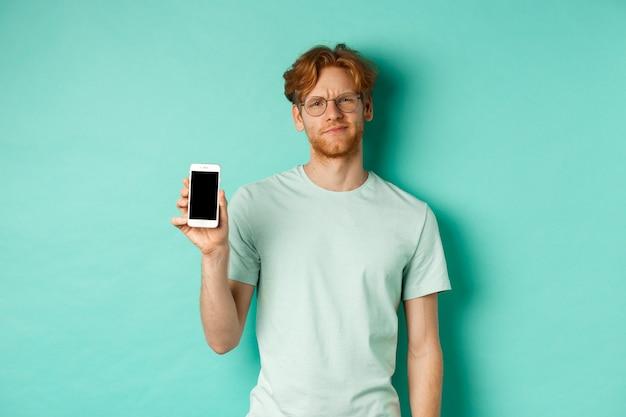 Modelo masculino escéptico con cabello rojo y gafas, mostrando la pantalla del móvil y frunciendo el ceño, decepcionado, no le gusta la aplicación, de pie sobre un fondo turquesa.