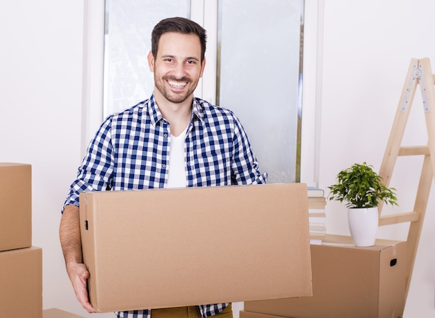 Modelo masculino feliz con caja de papel mientras se muda al nuevo apartamento