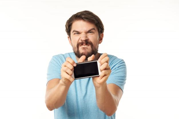 Modelo masculino guapo con barba con un teléfono posando en studio