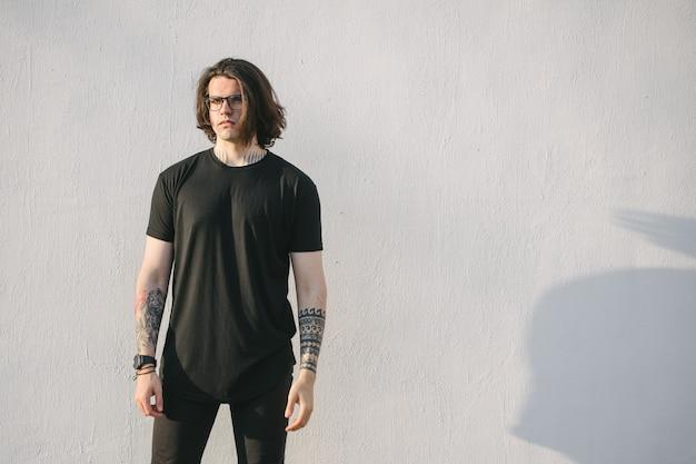 Modelo masculino guapo hipster con gafas con camiseta negra en blanco