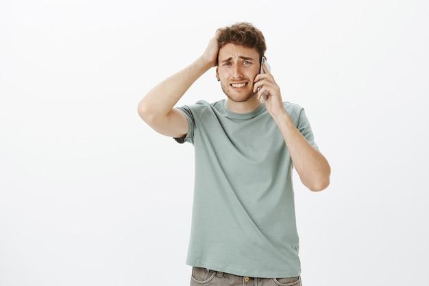 Modelo masculino guapo molesto y preocupado con cabello rubio, fruncir el ceño y apretar los dientes, tocar el cabello, sostener el teléfono inteligente cerca de la oreja, escuchar noticias terribles y estar triste
