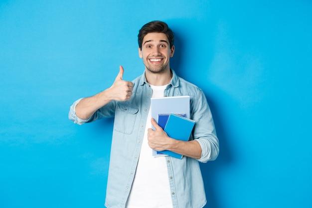 Modelo masculino joven feliz sosteniendo cuadernos y mostrando el pulgar hacia arriba complacido, sonriendo y recomendando cursos, de pie sobre fondo azul