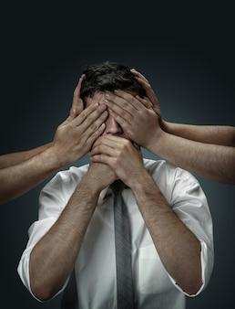 Un modelo masculino rodeado de manos como sus propios pensamientos en la pared oscura. un joven duda, no puede elegir la decisión correcta. concepto de problemas mentales, problemas en el trabajo, indecisión.