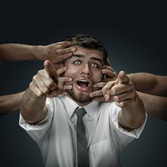 Modelo masculino rodeado de manos como sus propios pensamientos sobre fondo oscuro.