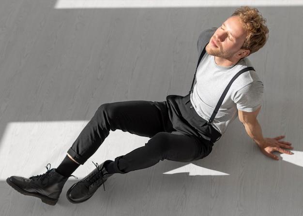 Modelo masculino sentado en el piso vista alta
