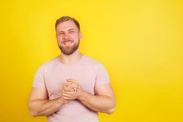 Modelo masculino con una sonrisa y las manos delante de él, sobre un fondo amarillo, con espacio para texto, con una emoción amistosa, copia espacio. el concepto es una buena oferta, la solución correcta.