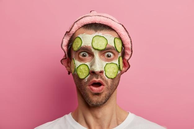 Modelo masculino sorprendido mira fijamente con los ojos abiertos y la boca