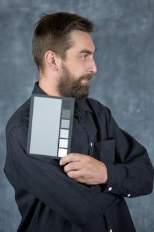 Un modelo masculino sostiene un comprobador de color con tonos grises neutros en sus manos