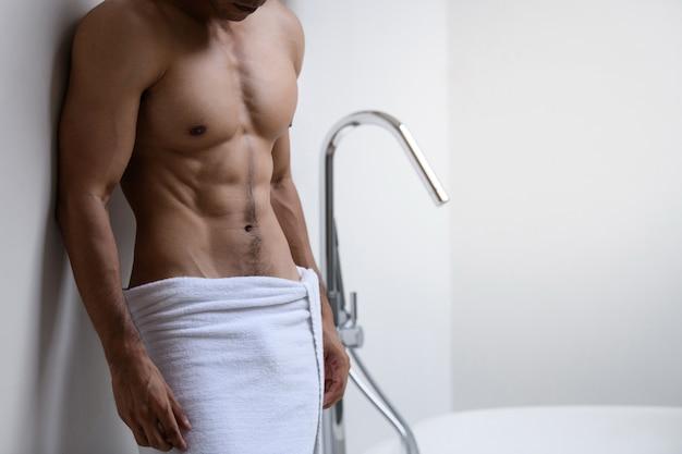 Modelo masculino con toalla blanca en baño.