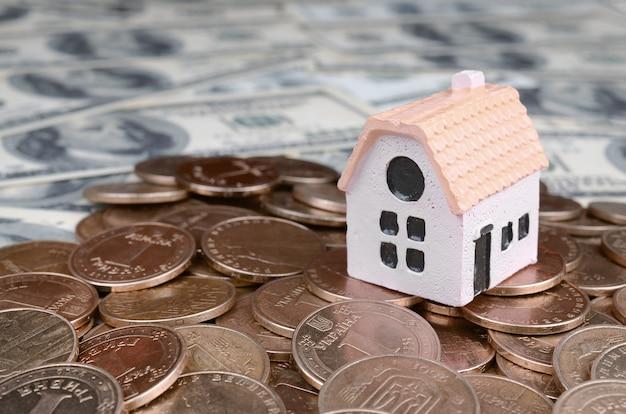 Modelo de mini casa en la pila de monedas grandes en muchos billetes de dólar