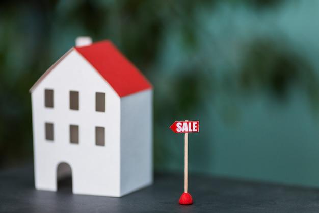 Modelo en miniatura de las propiedades inmobiliarias de la casa en venta contra el fondo borroso