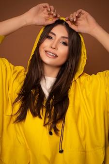 Modelo de moda en algodón amarillo con capucha