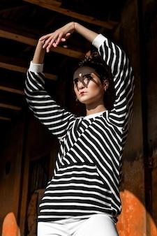 Modelo de moda de belleza girl con cabello castaño sobre un fondo de un edificio antiguo y abandonado, vistiendo ropa elegante.