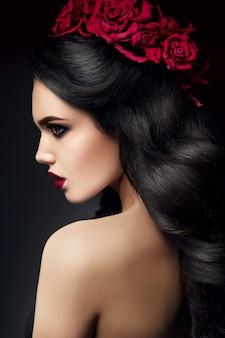 Modelo de moda de belleza girl portrait con peinado de rosas. labios rojos.