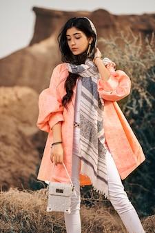 Modelo de moda en chaqueta coral y chal negro