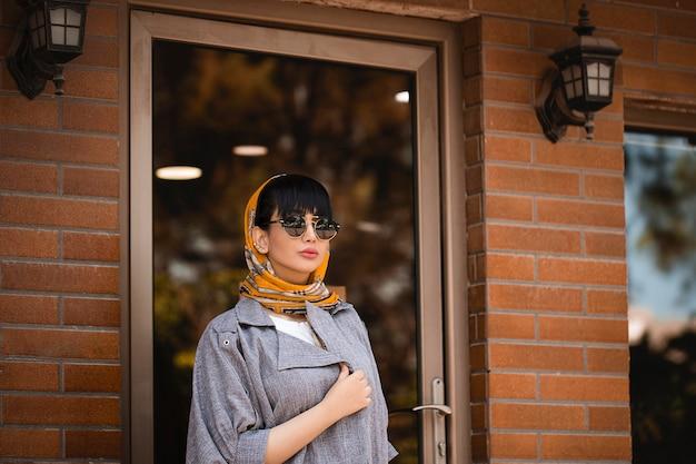 Modelo de moda en chaqueta gris y chal naranja con gafas de sol