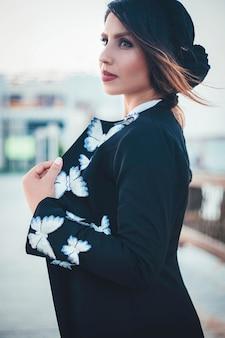 Modelo de moda en chaqueta de punto negro cálido con estampados blancos