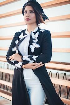 Modelo de moda en chaqueta de punto negro con mariposas y jeans blancos
