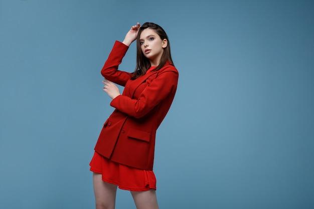 Modelo de moda en falda de chaqueta de traje rojo hermosa mujer joven disparo de estudio fondo azul