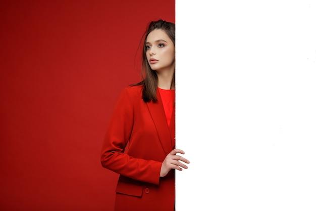 Modelo de moda en falda de chaqueta de traje rojo hermosa mujer joven fondo rojo