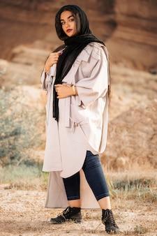 Modelo de moda en gabardina blanca, zapatillas negras y jeans azules