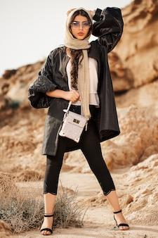 Modelo de moda en gabardina negra y bolso beige