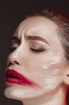 Modelo de moda girl con la cara pintada de color. retrato de arte de moda de belleza de mujer hermosa con maquillaje abstracto colorido.