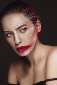 Modelo de moda girl con la cara pintada de color.