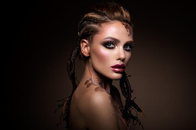 Modelo de moda con maquillaje brillante y brillo colorido