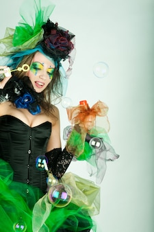 Modelo de moda con maquillaje creativo soplando pompas de jabón.
