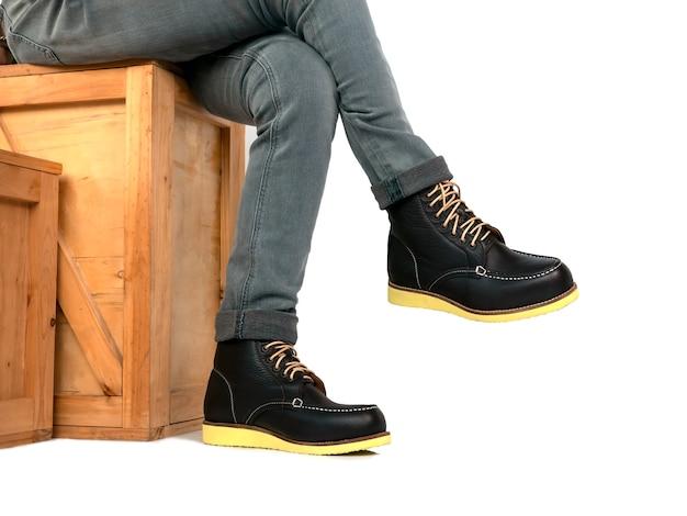 Modelo de moda masculina con botas de cuero negro y jeans sentado en caja de madera