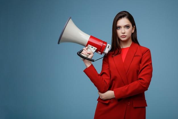 Modelo de moda con megáfono en falda de chaqueta de traje rojo hermosa mujer joven fondo azul