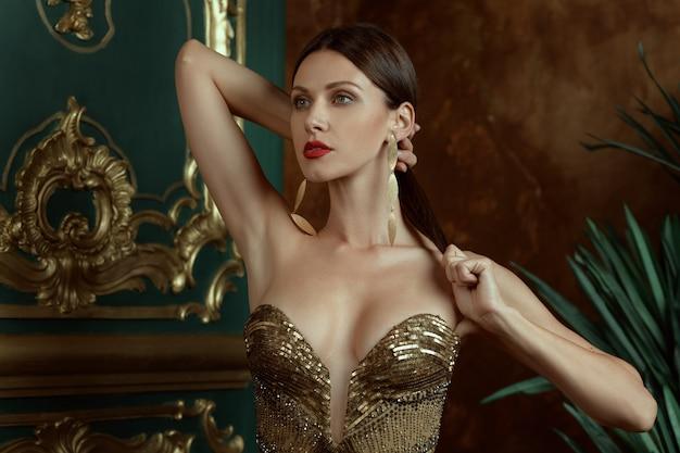 Modelo de moda de mujer morena morena de lujo con aretes dorados y collar de cadena en el vestido de escote que fija la cola del cabello con las manos y mira hacia adelante en el interior de diseño vintage con arbusto