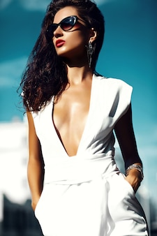 Modelo de moda mujer niña en traje blanco con gafas de sol en la calle