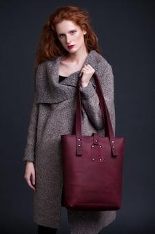Modelo de moda de pelo rojo con gran bolso de cuero rojo oscuro sobre fondo oscuro. chica con puente largo.
