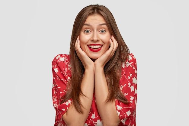 Modelo de moda positivo con maquillaje, labios rojos, vestido con ropa elegante, mantiene las manos en las mejillas, tiene una sonrisa con dientes