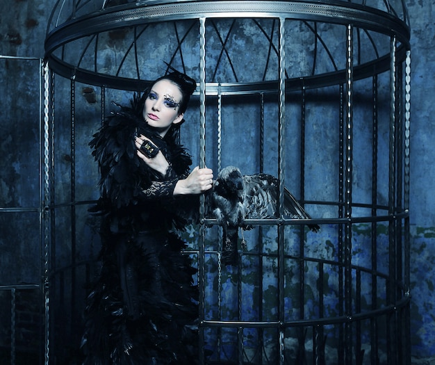 Modelo de moda en traje de fantasía posando en jaula de acero.