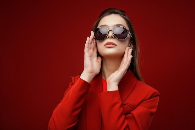 Modelo de moda en traje rojo chaqueta falda gafas de sol hermosa mujer joven fondo rojo